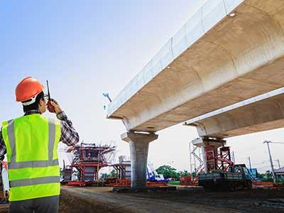 un uomo con un giubbotto fluorescente accanto a un ponte nella fase di costruzione