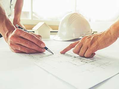 due mani che puntano su un disegno tecnico