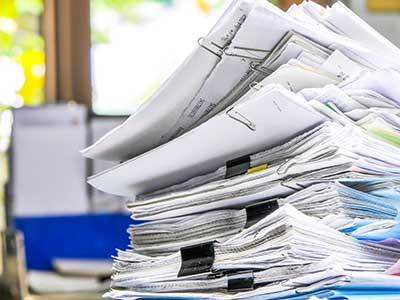 serie di documenti accatastati su un tavolo