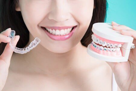 Braces — Girl Holding Cosmetic Enhancement in Owensboro, KY