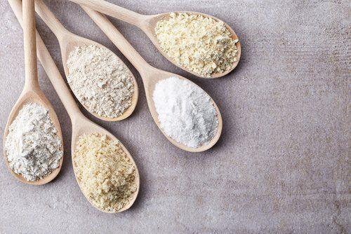 cinque cucchiai in legno con diversi tipi di farine