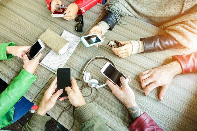 persone con cellulari in mano sedute al tavolo