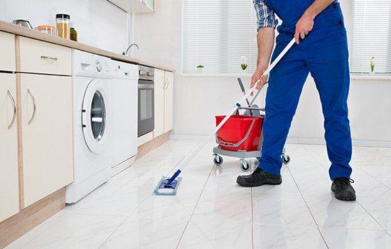 Un uomo in tuta blu sta pulendo il pavimento di una cucina con un mocio in microfibra ea fianco un cartello rosso
