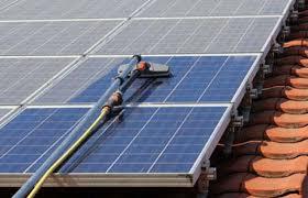 Vista ravvicinata di una mano con mocio che pulisce pannelli solari
