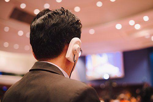 uomo di spalle con auriicolare bianco all`orecchio ascolta la videoconferenza
