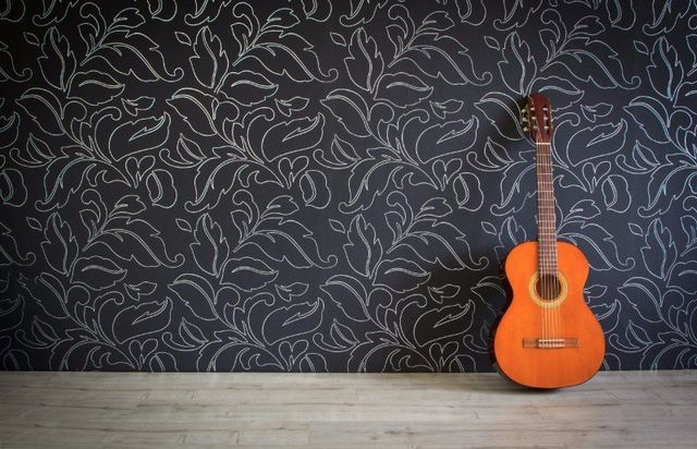 Chitarra su suolo di legno contro parete nera con design bianco de foglie