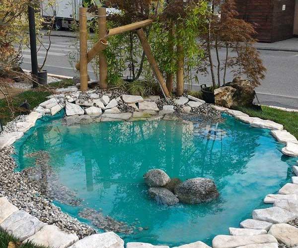 una pozza d'acqua artificiale , molto pulita contornata da dei sassi in un giardino a Candiana