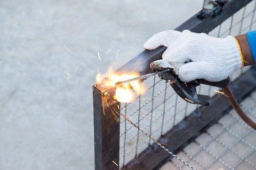 mano con guanto di protezione che effettua una saldatura sull'angolo di una gabbia di ferro
