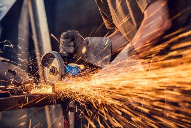 dettaglio di un operaio impegnato nella lavorazione di un elemento metallico