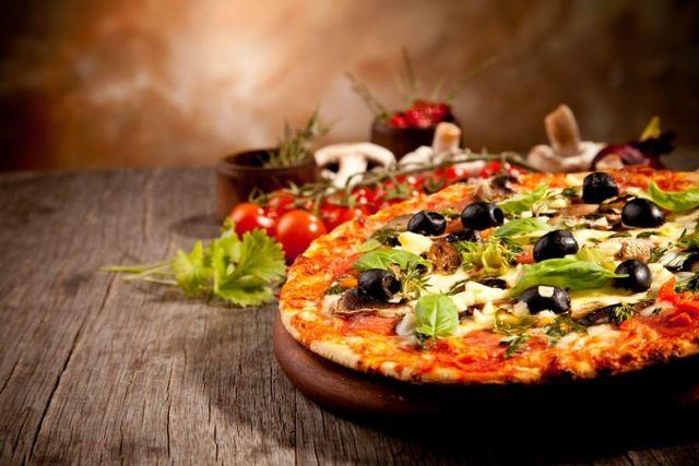 una pizza con olive nere , basilico e pomodoro