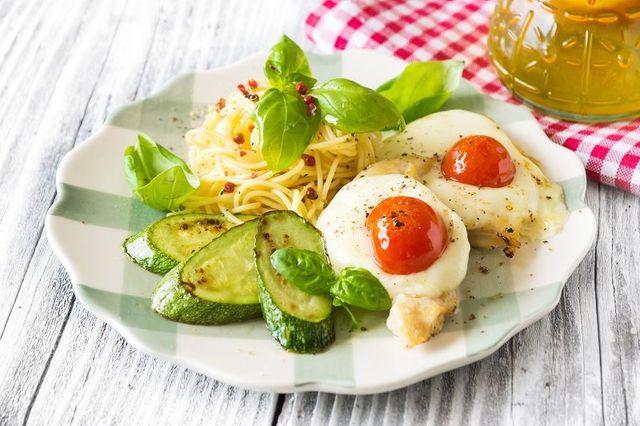 un piatto bianco con spaghetti, fette di zucchine e uova