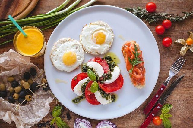 un piatto con pomodoro, mozzarella, salmone e uova all' occhio di bue