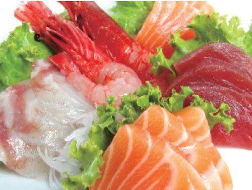 Due gamberi rossi, fette di tonno, salmone e altro pesce crudo