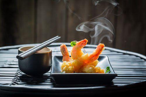 Piatto di gamberi fritti fumante con accanto una ciotola con sopra delle bacchette nere