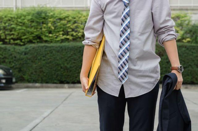 una persona con una cravatta, un raccoglitore e una giacca in mano