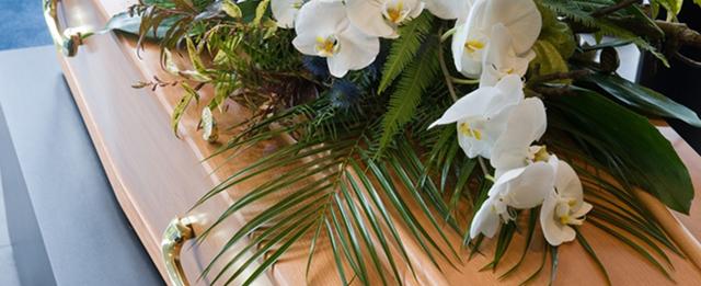 fiori bianchi e foglie su una bara