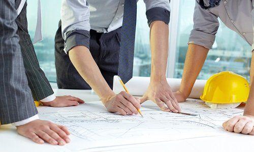 un uomo con una matita in mano con davanti un progetto edile e accanto altre persone