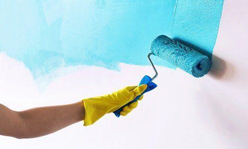 operaio durante una verniciatura azzurro sul muro