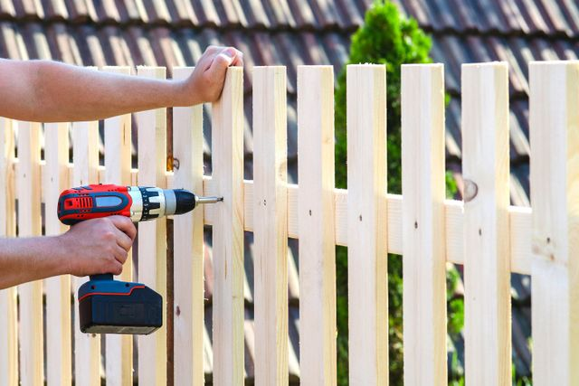 operaio lavora con trapano sul parapetto in legno