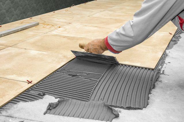 un uomo sta stendendo il cemento per il piastrellamento della superficie