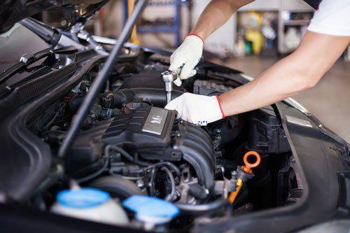 un meccanico che sta avvitando un bullone nella zona motore di un veicolo
