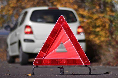 un triangolo rosso e in lontananza una macchina bianca