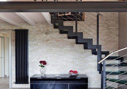 delle scale in metallo e un muro con le piastrelle ad effetto pietra