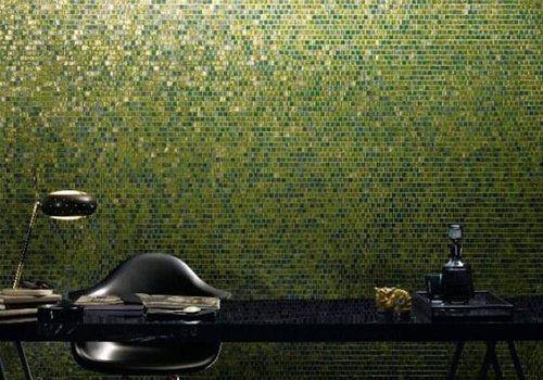 una scrivania, una sedia nera e un muro con piastrelle verdi brillanti
