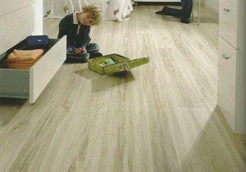 un bambino seduto su un pavimento in legno