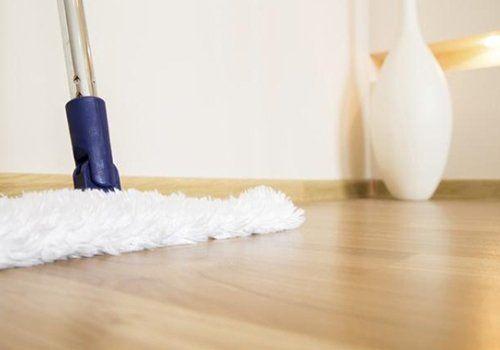 un scopa con un panno in microfibra e un pavimento in parquet