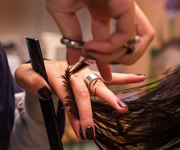 Un parrucchiere mentre taglia i capelli di una donna con una forbice