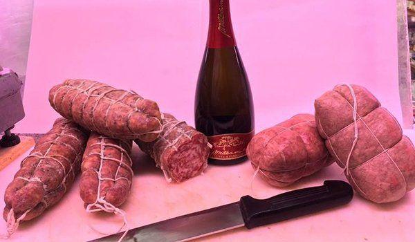 un tagliere con dei salami,una bottiglia di vino e un coltello