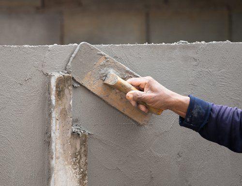 mano che assicura lo stucco sul muro con una paletta