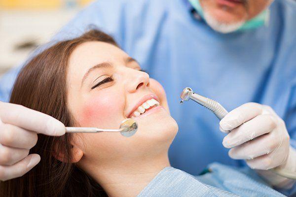 Dentista facendo un trattamento odontoiatrico su una paziente