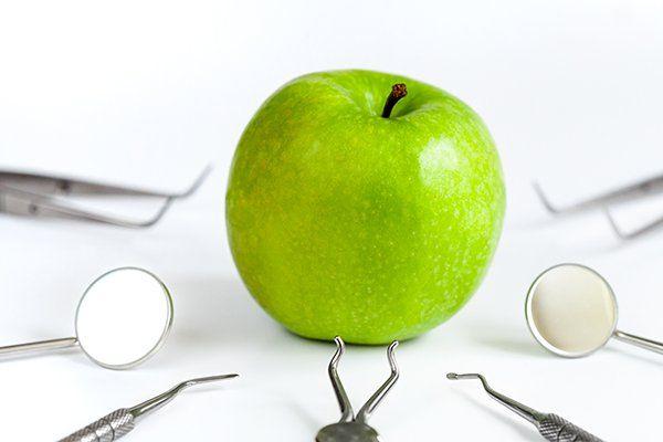 strumenti dentali con la mela su sfondo bianco vista superiore
