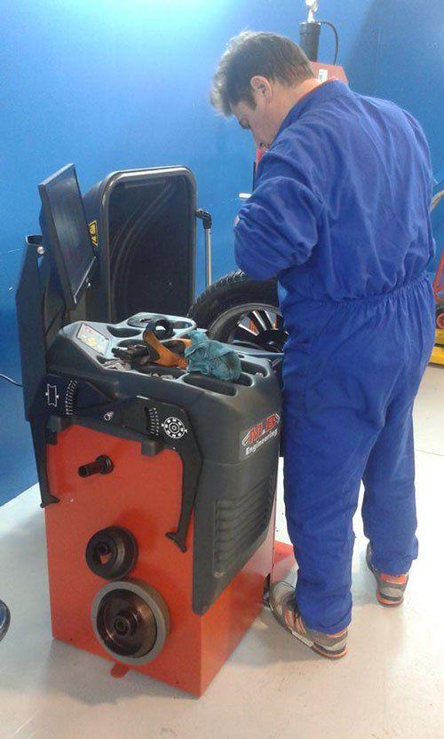 Uomo in tuta blu da meccanico che lavora su uno pneumatico