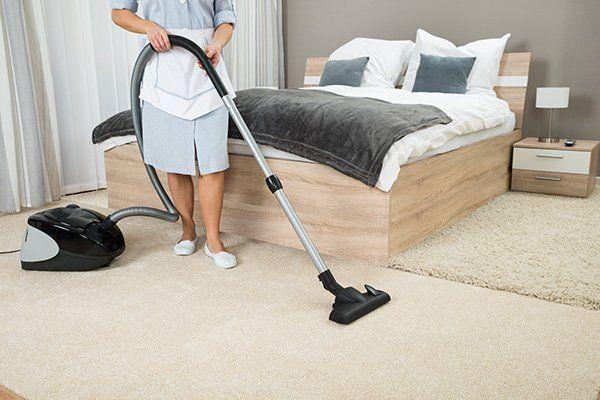 Una signora che utilizza l'aspirapolvere in camera da letto