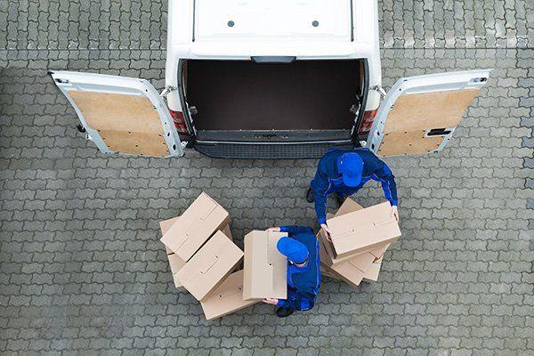 Due facchini che scaricano degli scatoli da un furgone bianco