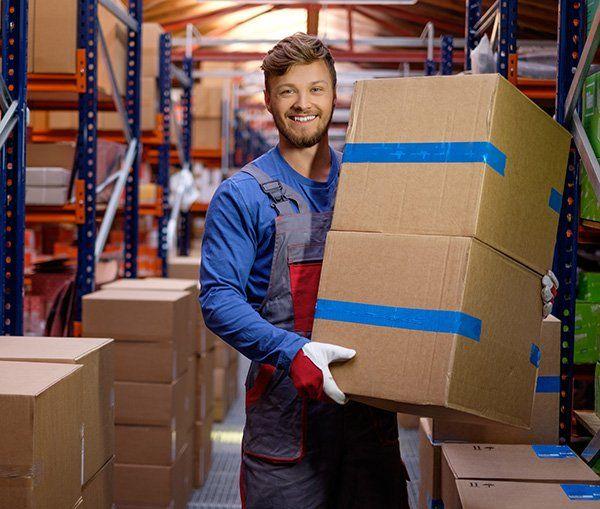 Un magazziniere che regge in mano due scatoli