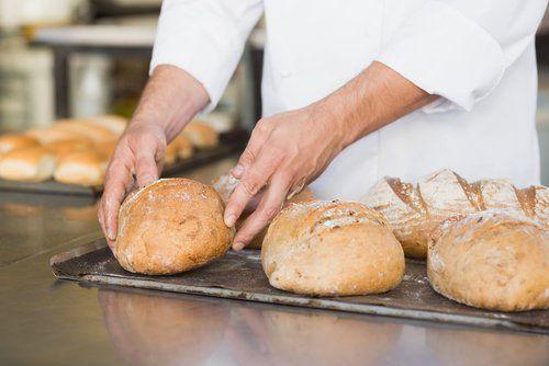 panettiere mentre controlla degli pane appena sfornato nella cucina della panetteria