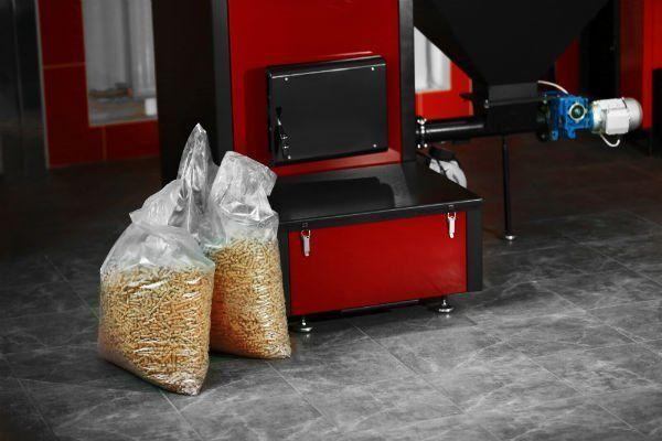 Stufa a pellet di colore rosso con sacchetti pieni di pellet sul pavimento