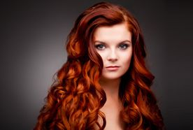 A lady with long dark red hair in ringlets