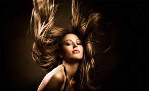 A lady with long windblown golden brown hair