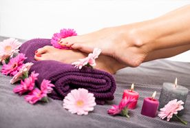 Ladies' feet resting on a rolled up purple towel surrounded by pink and purple flowers and candles