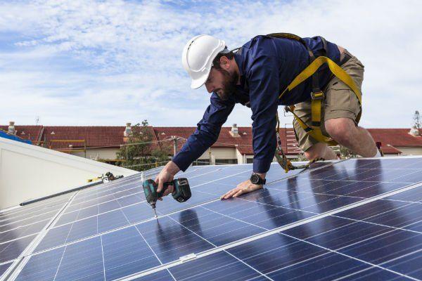 Tecnico del pannello solare con trapano che installa pannelli solari sul tetto