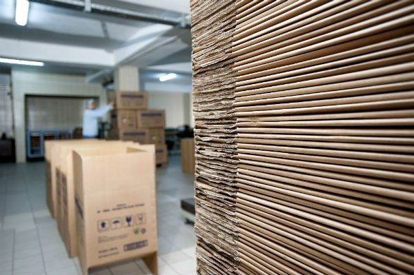 serie di scatole di cartone in un magazzino e un uomo al lavoro