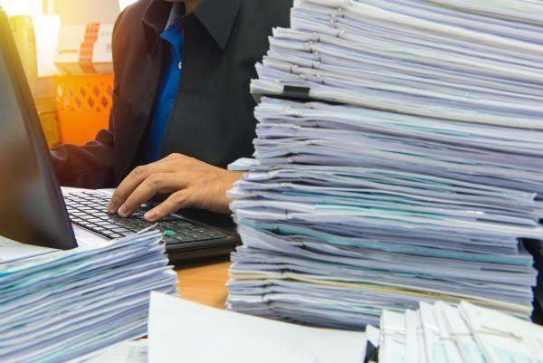 mano di un uomo che digita i tasti di una tastiera e una pila di documenti