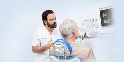 dentista analizza ortopantomografia con paziente
