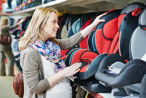 Donna incinta guardando un sedile di bambino per l'auto