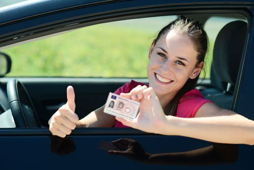 una ragazza che mostra la patente di guida